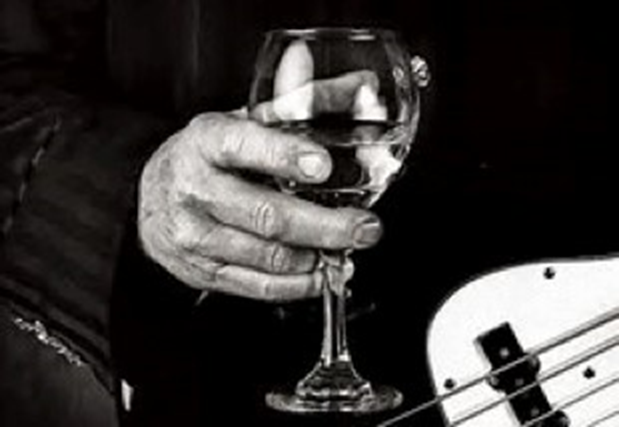Wine glass being held next to a guitar